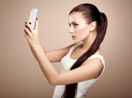 Schöne junge Frau, Selfie. Mädchen selbst das Fotografieren mit Handy. Beauty Mode. Wimpern. Kosmetische Augenschminke