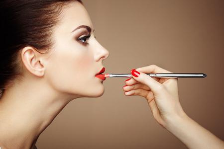 Make-up artiest toepassing lippenstift. Mooie vrouw gezicht. Perfecte make-up