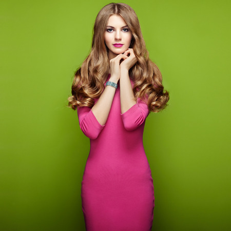 Fashion portrait of elegant woman with magnificent hair. Blonde girl. Perfect make-up. Girl in pink dress on green background Stock Photo