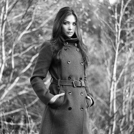topcoat: Portrait of young beautiful woman in autumn coat. Fashion photo. Black and white