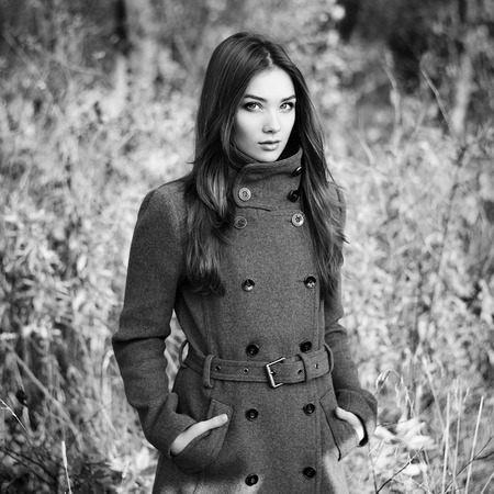 greatcoat: Portrait of young beautiful woman in autumn coat. Fashion photo. Black and white