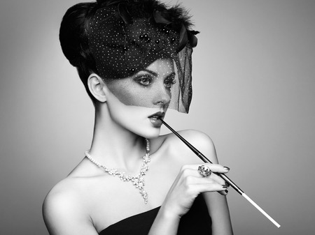 Portrait of beautiful sensual woman with elegant hairstyle.  Woman with cigarette Perfect makeup. Fashion photo. Black and white photo