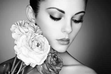 Portré gyönyörű fiatal nő, virágokkal. Tökéletes smink. Tökéletes bőr. Divat fotó. Fekete és fehér