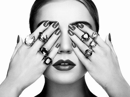 Portrait of beautiful woman with jewelry. Manicure and makeup. Perfect skin. Fashion beauty. Ring. Blonde girl. Close up. Black and white photo