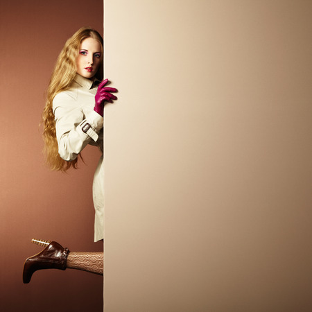Photo young beautiful woman in a raincoat in interior. Conceptual fashion. Text background photo