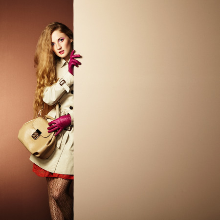 purse: Photo young beautiful woman in a raincoat in interior. Conceptual fashion. Text background