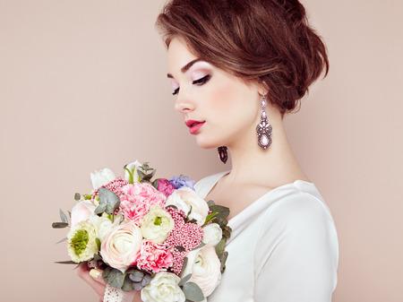 彼女の手で花の花束を持つ女性。花。春。花嫁。3 月 8 日。ファッション写真