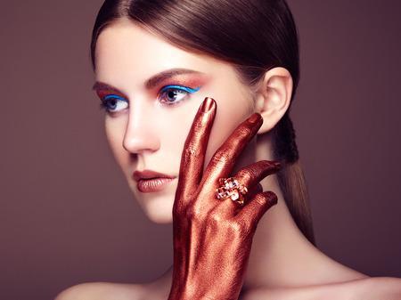 Portrait of beautiful young woman with art make-up. Bronze hand. Beauty fashion photo