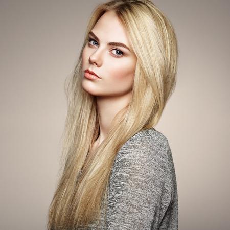 壮大な髪のエレガントな女性のファッションの肖像画。ブロンドの女の子。完璧なメイク。髪型