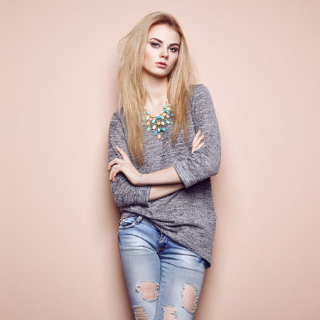 Fashion portrait of beautiful young woman with blond hair. Girl in blouse and jeans. Jewelry and hairstyle