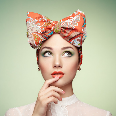 of cosmetics: Portrait of beautiful young woman with bow. Brunette girl. Beauty fashion. Cosmetic make-up