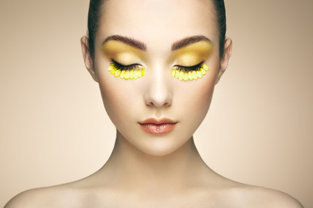 petal: Face of beautiful woman decorated with flowers. Perfect makeup. Beauty fashion. Eyelashes. Cosmetic Eyeshadow