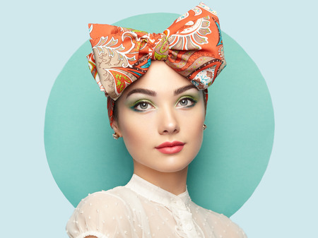 Portrait of beautiful young woman with bow. Brunette girl. Beauty fashion. Cosmetic make-up