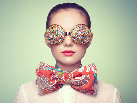 Retrato de la hermosa mujer joven con gafas de color. Manera de la belleza. Maquillaje perfecto. Decoración colorida. Joyas