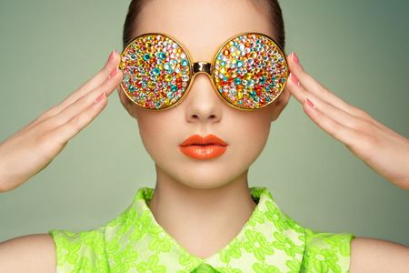 glamour luxury: Portrait of beautiful young woman with colored glasses. Beauty fashion. Perfect make-up. Colorful decoration. Jewelry