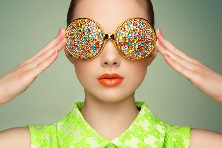 Portret van mooie jonge vrouw met een gekleurde bril. Schoonheid mode. Perfecte make-up. Kleurrijke decoratie. Juwelen Stockfoto - 40214204