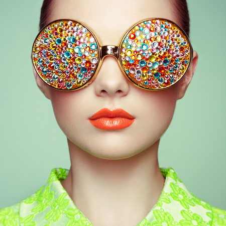 pose: Portrait of beautiful young woman with colored glasses. Beauty fashion. Perfect make-up. Colorful decoration. Jewelry