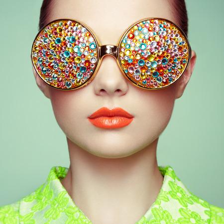 salon de belleza: Retrato de la hermosa mujer joven con gafas de color. Manera de la belleza. Maquillaje perfecto. Decoración colorida. Joyas