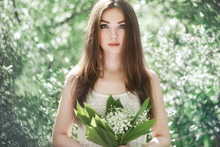 lily of the valley: Portrait of beautiful young woman with lily of the valley. Girl on nature. Spring flowers. Fashion beauty Stock Photo
