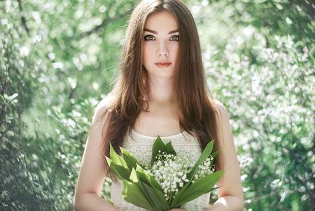 Portret van mooie jonge vrouw met lelie van de vallei. Meisje op de natuur. Lente bloemen. Fashion schoonheid