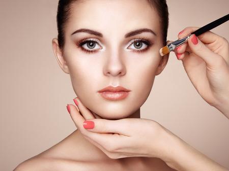 nude pose: Makeup artist applies skintone. Beautiful woman face. Perfect makeup. Skincare foundation