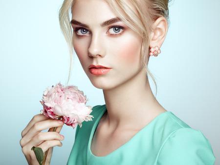 maquillage: Portrait de la belle femme sensuelle avec coiffure �l�gante. Maquillage parfait. Jeune fille blonde. photo de mode. Fleurs