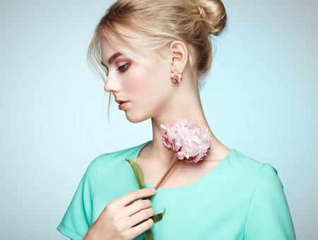 エレガントなヘアスタイルと美しい官能的な女性の肖像画。 完璧なメイク。ブロンドの女の子。ファッション写真。花