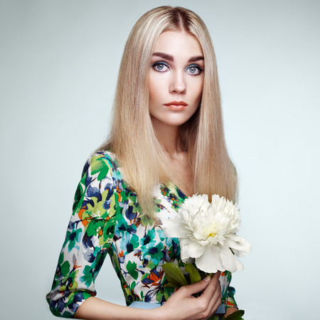 ladylike: Fashion portrait of elegant woman with summer flowers. Blonde girl. Perfect make-up. Hairstyle. Summer dress. Peonies