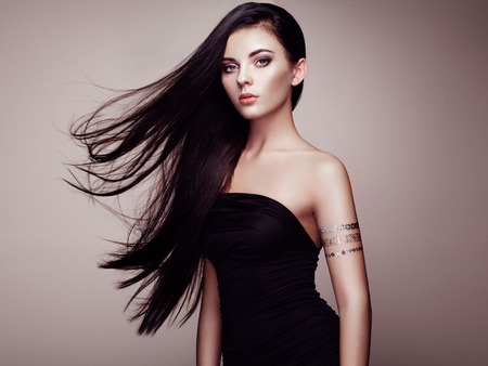 壮大な髪とエレガントな女性のファッション ポートレート。ブルネットの少女。完璧なメイク。エレガントなドレスの女の子。タトゥー ゴールドを 写真素材