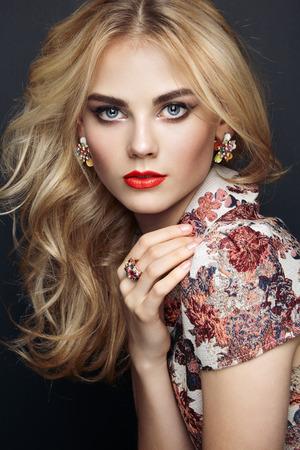 유행: 우아한 헤어 스타일을 가진 아름 다운 관능적 인 여자의 초상화입니다. 완벽한 메이크업. 금발의 소녀. 패션 사진. 보석과 드레스