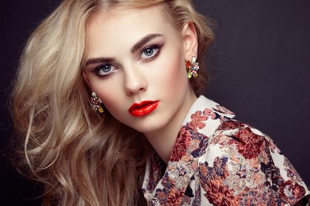 trend: Portrait of beautiful sensual woman with elegant hairstyle.  Perfect makeup. Blonde girl. Fashion photo. Jewelry and dress