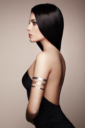 брюнетка: Мода портрет элегантной женщины с великолепным волосами. Брюнетка девушка. Идеальный макияж. Девушка в элегантном платье. Вспышка татуировки золото