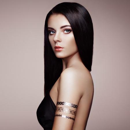 femme brune sexy: Fashion portrait de femme élégante aux cheveux magnifiques. Brunette fille. Maquillage parfait. Jeune fille en robe élégante. Or flash de tatouage