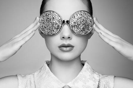 Portret van mooie jonge vrouw met een gekleurde bril. Beauty fashion. Perfecte make-up. Kleurrijke decoratie. Sieraden. Zwart en wit