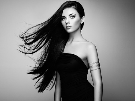 charm: Fashion portrait of elegant woman with magnificent hair. Brunette girl. Perfect make-up. Girl in elegant dress. Flash tattoo gold. Black and white