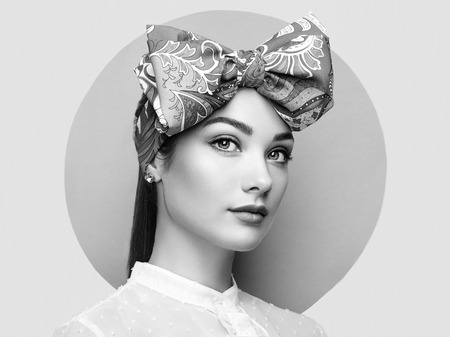 fashion girl: Portrait of beautiful young woman with bow. Brunette girl. Beauty fashion. Cosmetic make-up. Black and white