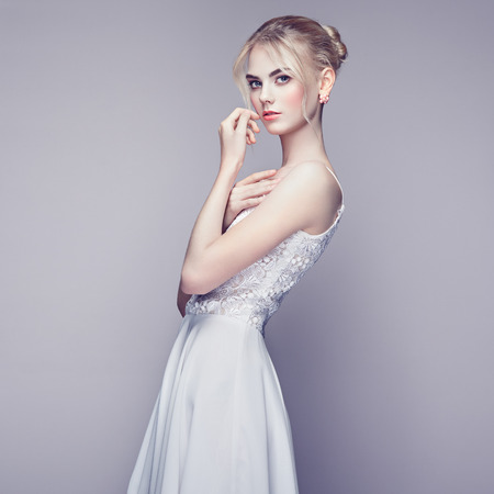 Fashion portrait of beautiful young woman with blond hair. Girl in white dress on white background