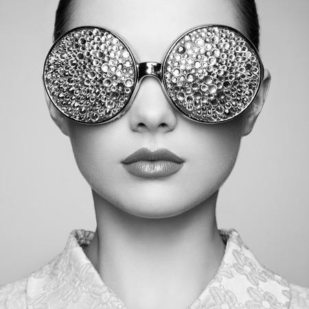 メガネと美しい若い女性の肖像画。美容ファッション。完璧なメイク。カラフルな装飾。ジュエリー。黒と白