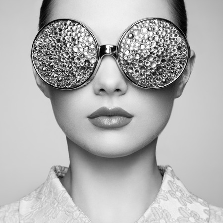 fashion: Portrait of beautiful young woman with colored glasses. Beauty fashion. Perfect make-up. Colorful decoration. Jewelry. Black and white