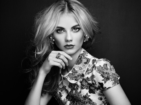 Portrait of beautiful sensual woman with elegant hairstyle.  Perfect makeup. Blonde girl. Fashion photo. Jewelry and dress. Black and white Reklamní fotografie
