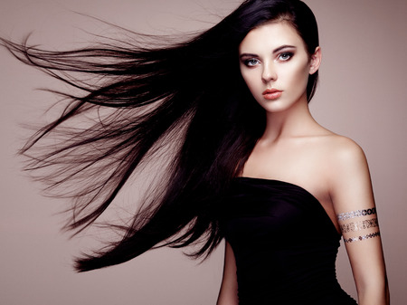Fashion portrait of elegant woman with magnificent hair. Brunette girl. Perfect make-up. Girl in elegant dress. Flash tattoo gold