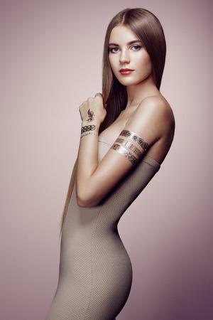 Retrato de moda de mujer elegante con el pelo magnífico. chica rubia. Maquillaje perfecto. Chica en vestido elegante. Oro del flash del tatuaje Foto de archivo - 45243782