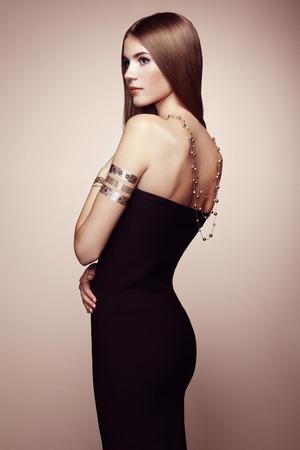 Moda ritratto di donna elegante, con i capelli magnifico. Ragazza bionda. Perfetto make-up. Ragazza in abito elegante. Oro flash tattoo Archivio Fotografico - 45393537