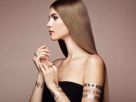 cabello rubio: Retrato de moda de mujer elegante con el pelo magn�fico. Chica rubia. Maquillaje perfecto. Chica en vestido elegante. Oro del flash del tatuaje