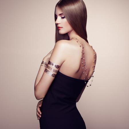 mujeres fashion: Retrato de moda de mujer elegante con el pelo magnífico. Chica rubia. Maquillaje perfecto. Chica en vestido elegante. Oro del flash del tatuaje