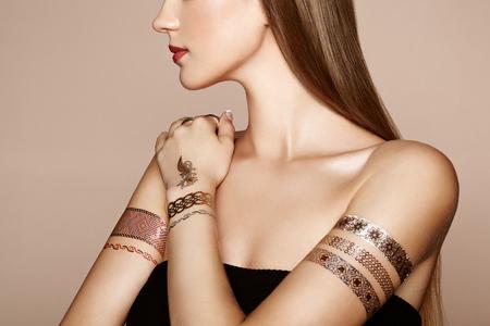 mujer elegante: Retrato de moda de mujer elegante con el pelo magn�fico. Chica rubia. Maquillaje perfecto. Chica en vestido elegante. Oro del flash del tatuaje