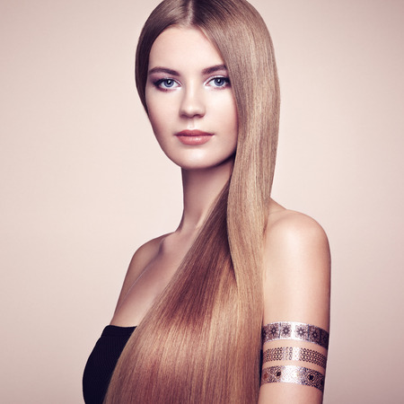 hair style: Fashion portrait of elegant woman with magnificent hair. Blonde girl. Perfect make-up. Girl in elegant dress. Flash tattoo gold