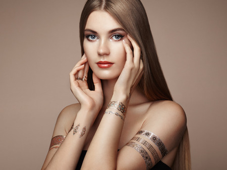 Fashion portrait of elegant woman with magnificent hair. Blonde girl. Perfect make-up. Girl in elegant dress. Flash tattoo gold