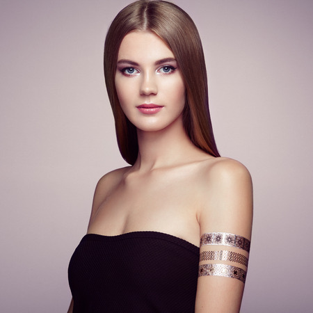 elegance: Fashion portrait of elegant woman with magnificent hair. Blonde girl. Perfect make-up. Girl in elegant dress. Flash tattoo gold