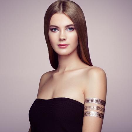 mujer elegante: Retrato de moda de mujer elegante con el pelo magnífico. Chica rubia. Maquillaje perfecto. Chica en vestido elegante. Oro del flash del tatuaje